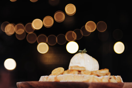 Waffle topped with vanilla ice cream and banana serve on wooden plate with bokeh background