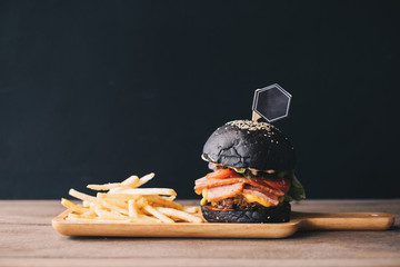 Charcoal burger made with black charcoal bun and sesame served with potato french fries on wooden rustic table. background is black grunge wall.