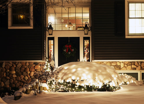 Winter holidays outdoor decoration background. Beautiful snowy night scene with porch and front yard of the house decorated by glowing in the dark garlands. Christmas and New Year holiday background.