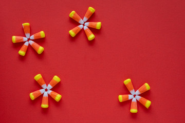 Halloween candy corn in star patterns on an orange background