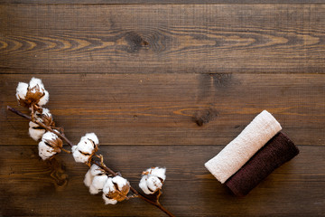 Spa concept. Set of towels twisted coil near cotton flowers on dark wooden background top view copy space