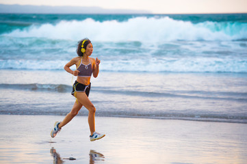 fit and athletic Asian Chinese sporty woman running on beautiful beach doing jogging workout on sunset in fitness healthy lifestyle and summer outdoors activity