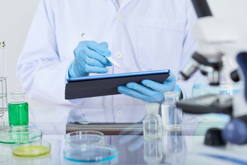 Laboratory worker entering information in digital tablet