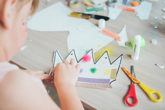 Pompons, paper crown, spangles. Project of children's creativity, handicrafts, crafts for kids.