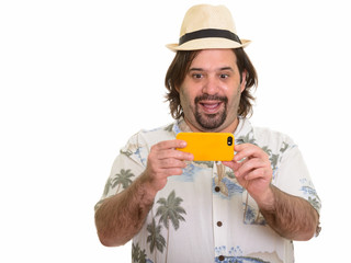 Happy fat Caucasian man smiling and taking picture with mobile phone