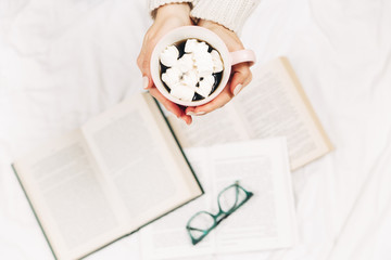 woman in bed and read book with cup of coffee.Stylish minimalist photo.Top view.