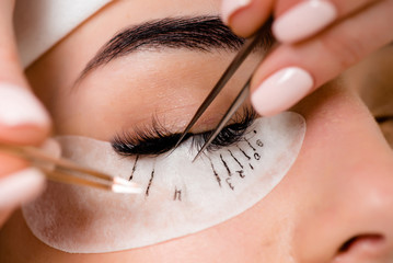 Eyelash extension procedure close up. Beautiful Woman with long lashes in a beauty salon.