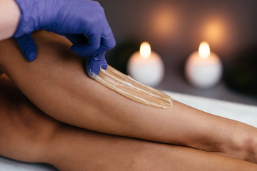 Midsection of beautician waxing woman's leg at salon