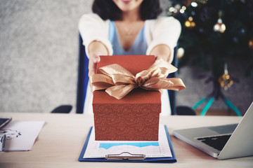 Cropped image on female entrepreneur outstretching hands with Christmas present