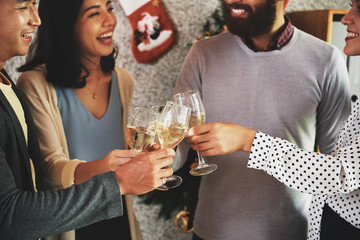 Group of joyful young people laughing and toasting with champagne glasses at Christmas party