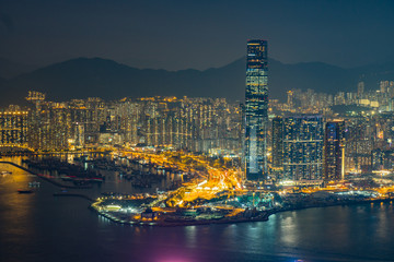 View of hong kong skyline at night, mountains in the background, modern skyscrapers at night