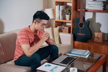 Pensive young entrepreneur reading e-mail on laptop screen