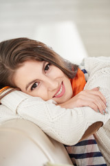 Smiling beautiful woman in cozy warm sweater looking at camera