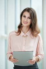 Smiling beautiful business woman holding folder with important documents