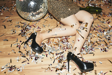 Cropped image of young woman in high heels and mini dress lying on the floor covered with confetti