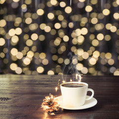 Cup of black coffee on wooden table in cafe. Blurred gold garland as background. Christmas Time. Image for display or montage your products.