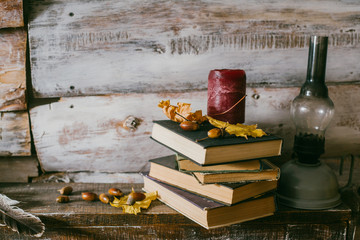 time to read books. books, candle and oli lamp on the table. wooden background. vintage.acorns