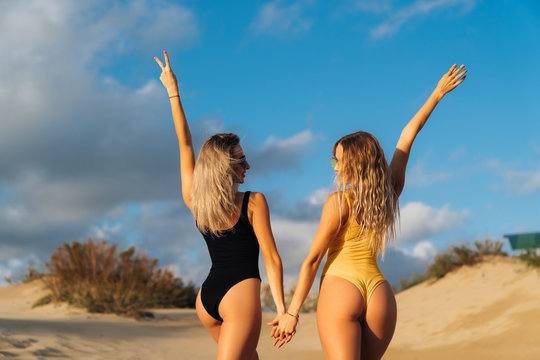 Couple of two model girl with a sexy figure in a swimsuit turned back to the camera, showing gestures of joy with hands. Woman traveler enjoys sunset on the beach with sand, elastic booty and body.