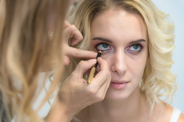 The work of a professional make-up artist, beautician, makes makeup on the face of a blonde girl with shadows on the eyes.