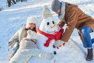 Familie baut einen Schneemann zusammen
