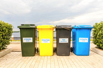 Containers for separate collection of garbage.Text in Russian: Glass. Plastic. Solid waste. Paper.