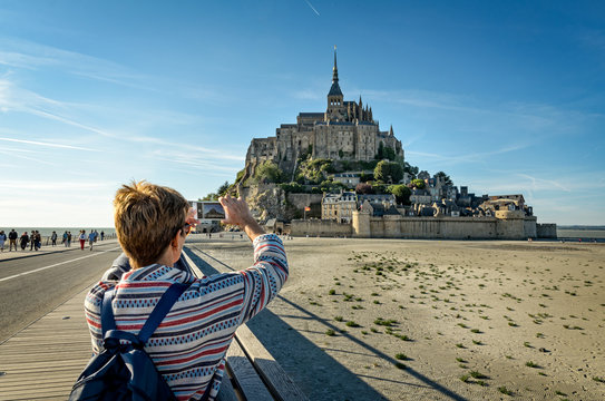 A tourist takes photos of Mont Saint Michel with her smartphone