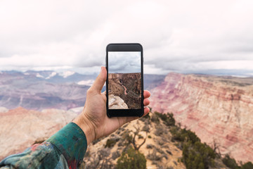 Person holding smartphone with Grand Canyon picture