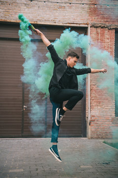young male contemporary dancer jumping in green smoke on urban street