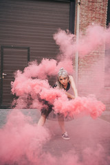attractive young woman dancing in pink smoke and looking at camera on street