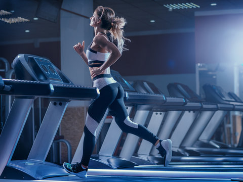 Woman trains on a treadmill in the gym. Young fitness girl running on treadmill machine. Sports exercises for weight loss.