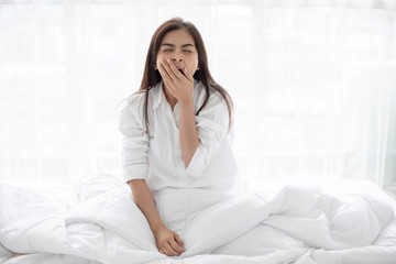 Asian woman Beautiful young smiling woman sitting on bed and stretching in the morning at bedroom after waking up in her bed fully rested and open the curtains in the morning to get fresh air. Wall mural
