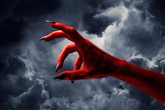 Halloween red devil monster hand with black fingernails against a dark sky