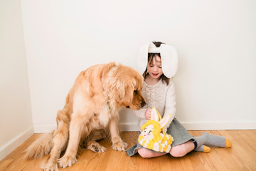Portrait of a smiling girl wearing bunny ears sitting on the floor with her dog