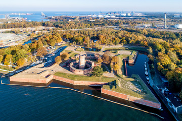 Medieval Wisloujscie Fortress with old lighthouse tower in port of Gdansk, Poland. A unique monument of the fortification works. Aerial view at sunset. Exterior Northern  Gdansk port in the background