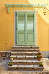 Stone stairs by wooden entrance door in old house of antique