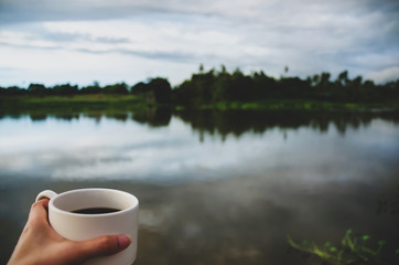 White coffee cup in hand At the waterfront in the morning.Morning coffee.Do not focus on objects.