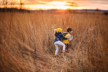 Boy and girl messing about in a field at sunset, United states