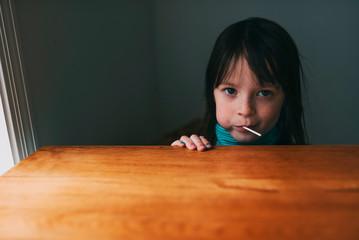 Portrait of girl eating lollipop at home