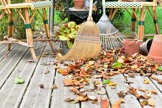broom and rake in leaves on wooden terrace