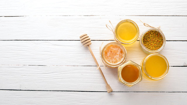 Set of bee products and honey on a white wooden background. Free space for text. Top view.