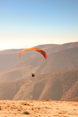 Paragliding in the Ukrainian Carpathians. People in parachute mountains. Autumn landscapes on a sunny day. Equipping for paragliding.Sportsmen.Sunsut and sunrise