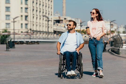 handsome boyfriend in wheelchair and girlfriend with coffee in paper cup having walk on street and looking away