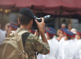 Man photographing soldiers in town square, Valletta, Malta