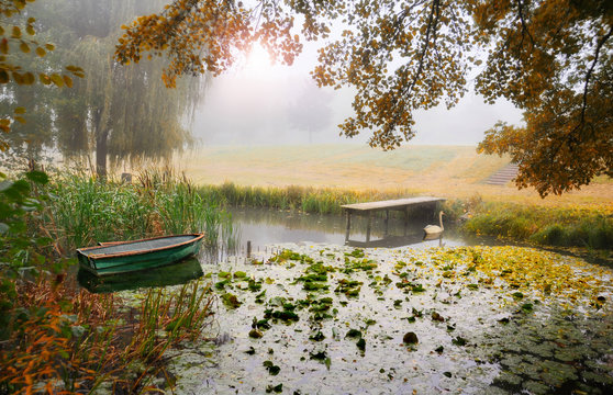 Boat moored on a river in the mist, France