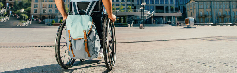 cropped panoramic view of man using wheelchair with bag on street