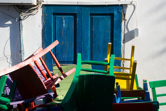 KAS, TURKEY Coloured chairs stacked in front of blue door.