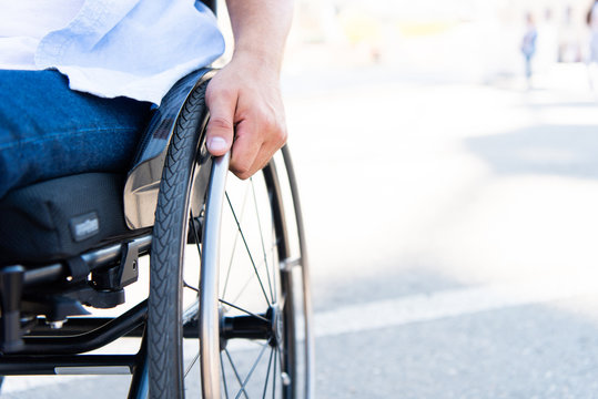 cropped image of man using wheelchair on street