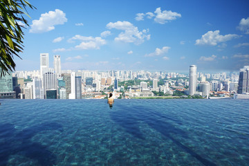 Back view of a beautiful woman relaxing in famous  infinity pool at  Marina Bay Sands hotel, October 16, 2018