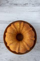 plain lemon bundt cake on cake stand flat lay