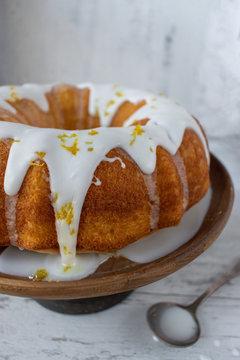 lemon bundt cake with white glaze on cake stand